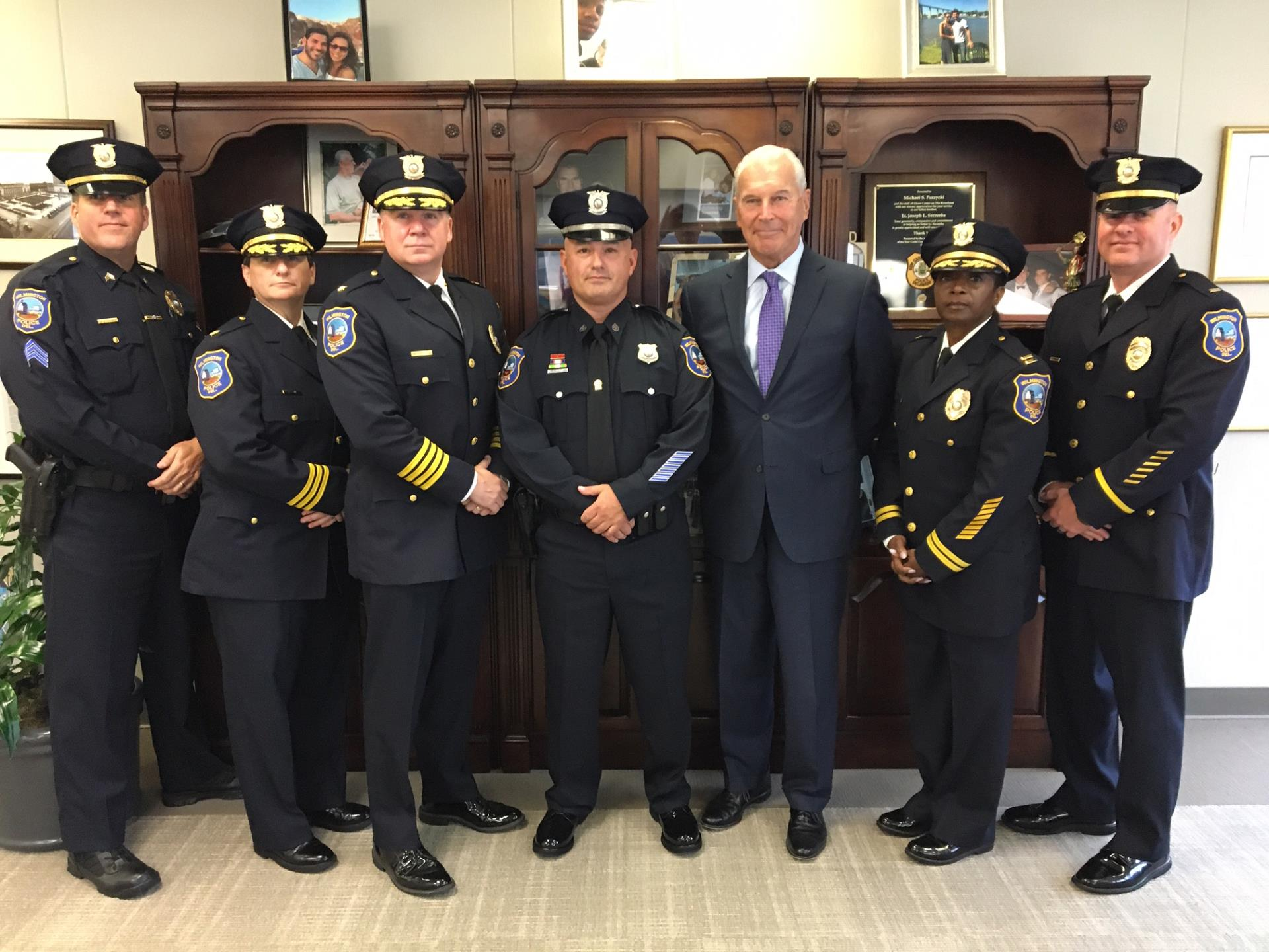 Photo of Master Sergeant Barry Mullins, Inspector Cecilia Ashe, Chief Robert J. Tracy, Detective Thomas Curley, Mayor Mike Purzycki, Captain Sherry Tull and Lieutenant Malcolm Stoddard